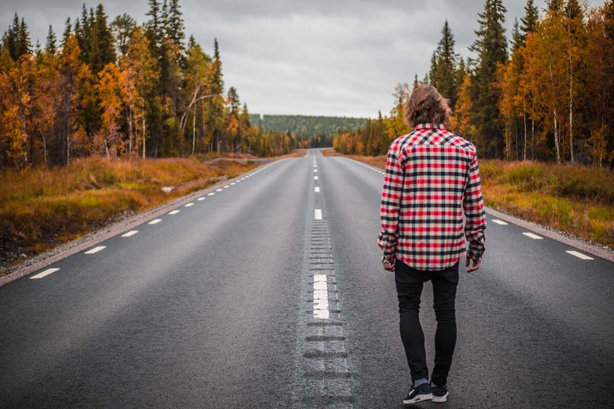 Young man looking out to the open road surrounded by forest
