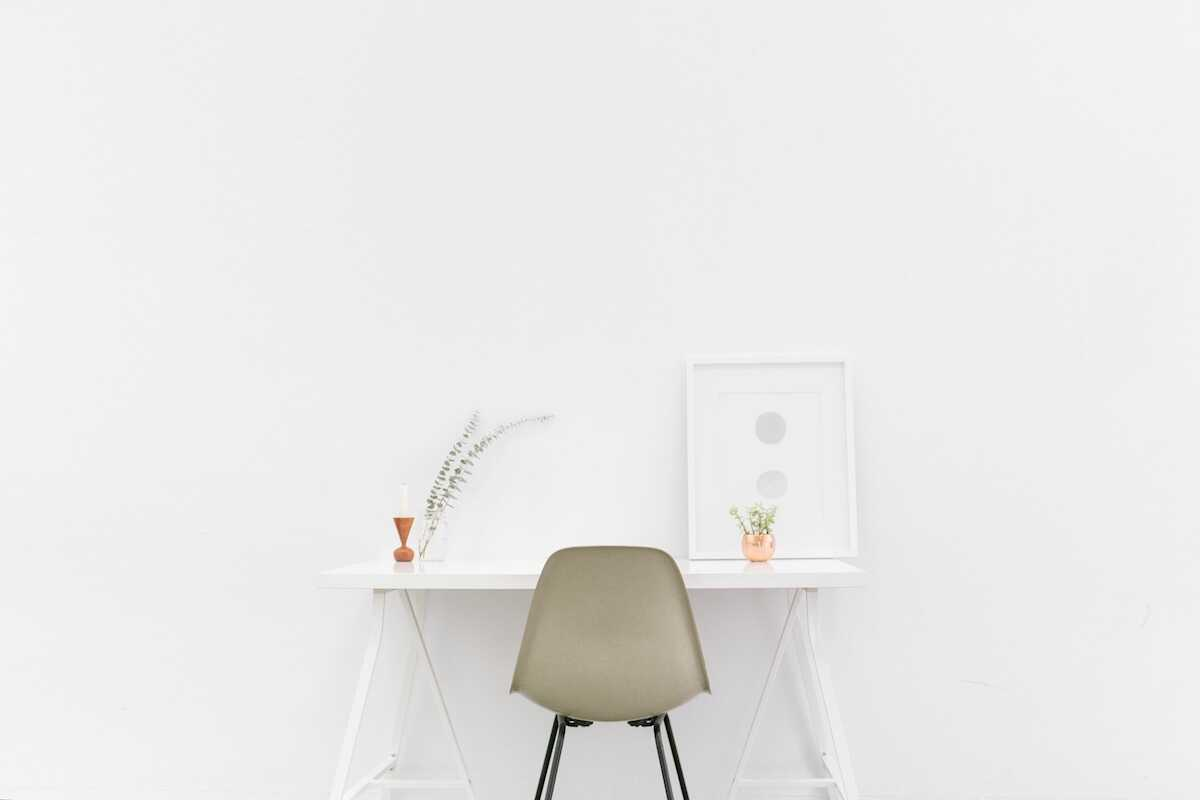 White home office desk with white chair in front of a white wall