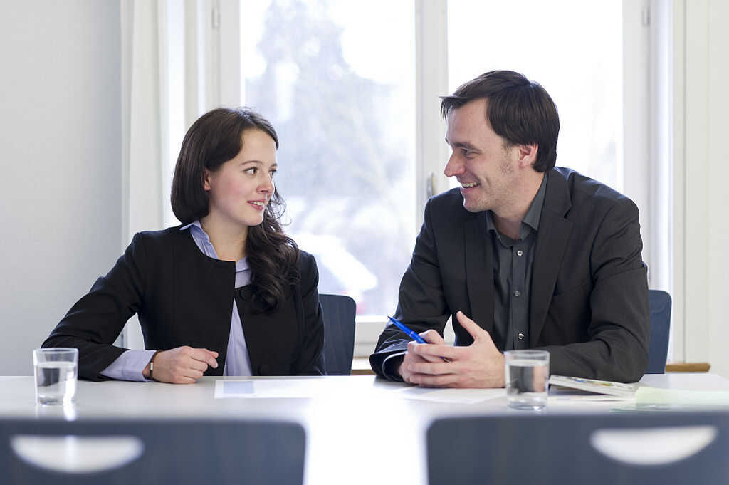 Man and woman talking to one another sitting at a meeting room table