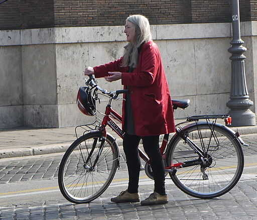 Professor Mary Beard wheeling a bicycle while filming in Rome